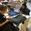 Penn State Green Teams members Barbara Taylor and Ashli Baker are making reusable cloth bags from cotton t-shirts at an event during Penn State's multi-week Earth Day(s) 2017 celebration.