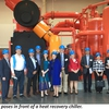 A tour group poses in front of one of the heat recovery chillers at the Central Energy Facility