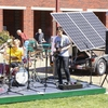"Student band ""Corporate Stepdads"" performs on a stage powered by solar panels."