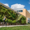 Photo of student cycling by green wall at NSCC Ivany Campus