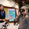 "Former Administrator of the EPA, Gina McCarthy, trys out a virtual reality project entitled ""Beach,"" created by Harvard Graduate School of Design students at the Harvard Sustainability Showcase. ""Beach"" is an interactive experience which allows the viewer to see how different parts of Harvard's campus will be affected by sea level rise."