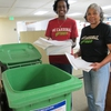 Two Stanford staff members take the extra step of bringing their paper waste to the recycling bin in the hallway.