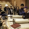 University of Calgary students gather round a sacred Torah scroll at the Beth Tzedec Synagogue in Calgary during the Kaleidoscope Project.