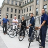The president of the University of Ottawa and employees from Facilities display the employee bicycle fleet