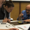 Sustain IT Workshop: Physics faculty member instructs  how to soder solar charger to Eco-Rep